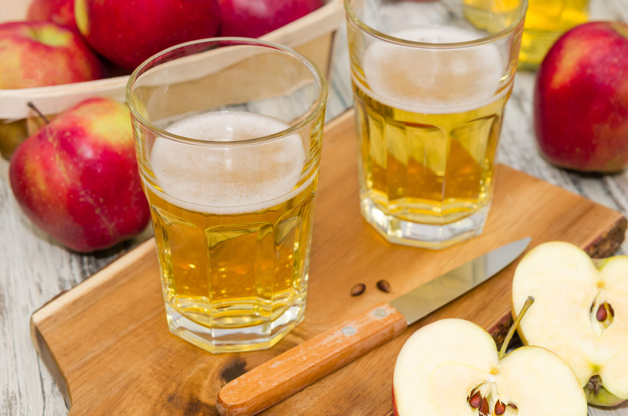 two glasses of cider with cut apples on a board
