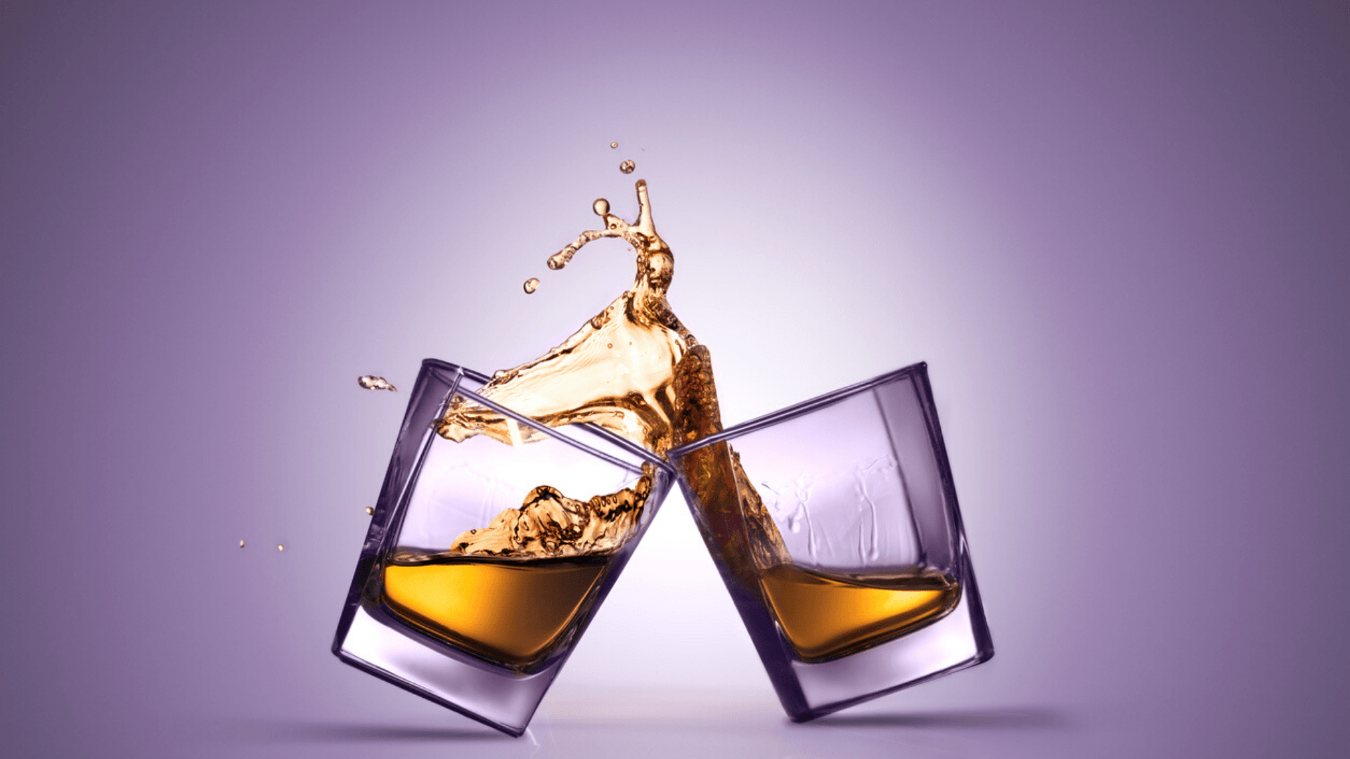Two glasses of whiskey splashing after a cheers.
